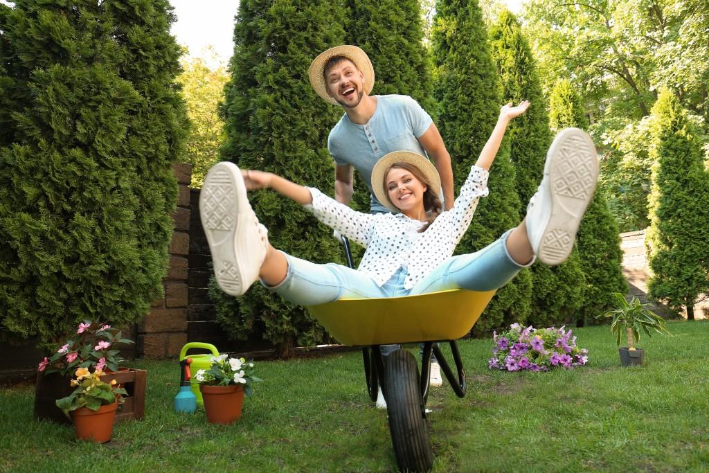 couple joyeux s_amusant au jardin - on adore - ces outils de jardinage pratiques auxquels on ne pense pas forcement
